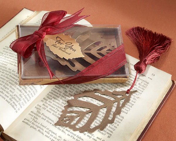"Turning Leaves Book Mark with Burgundy Tassel - Autumn has always been a romantic muse for great writers and poets. As you embark on a new chapter in your life during this glorious season, share the promise of a happy ending with this lovely leaf-shaped bookmark. The artistic, openwork metal design is enhanced by a rich burgundy silk tassel that perfectly complements the deep-rust color of the leaf a fall icon and the ideal place-keeper between the leaves of your guests favorite book. Each ""Turning Leaves"" bookmark measures 3.75inches and is impressively displayed in an autumn-leaves gift box complete with a clear top, a dainty, burgundy organza ribbon and a ""For You"" tag that replicates the leaf inside."