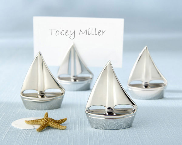 Shining Sails Silver Place Card Holders  - When the sea beckons, love sets sail near the splendor of a sun-drenched shore. Create the ambience only a beach wedding can inspire by making your tables an ocean full of glistening silver sailboats with these Shining Sails Place Card Holders, each one a paragon of stunning simplicity. The sailboats measure 1.50 x 1.25 x .50 inches. Sold as Sets of 4