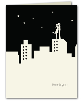 "A great note card that is designed with a black and white city scape and a couple standing on top of a building in an embrace.  The buildings windows are heart shaped to complete this stylish note card.  Includes ecru envelope. This note card is sold blank and does not have wording on the front.  If you would like ""thank you"" printed on the front please select the personalized option."